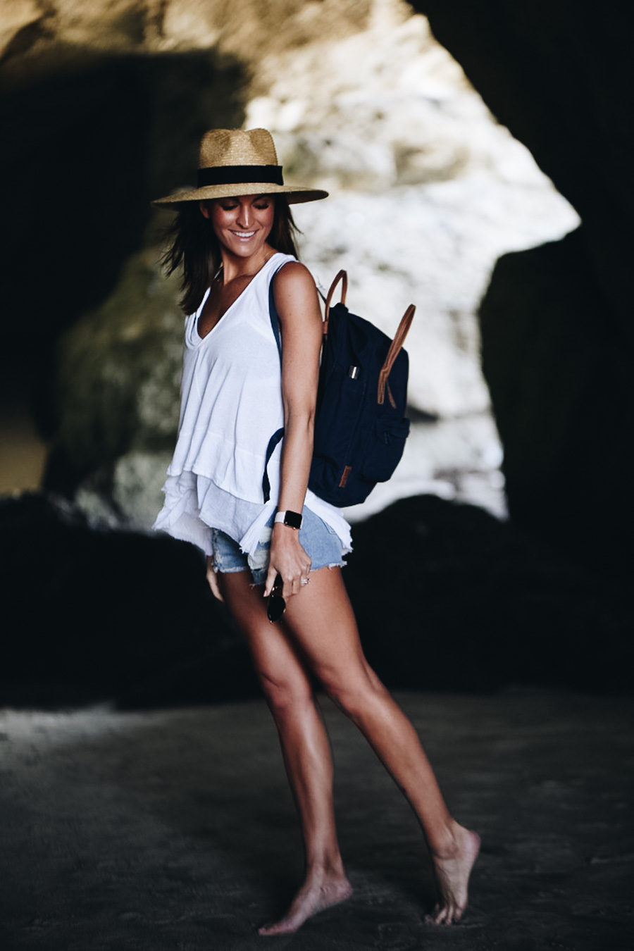 woman with fjallraven backpack exploring thousand steps beach sea cave laguna california